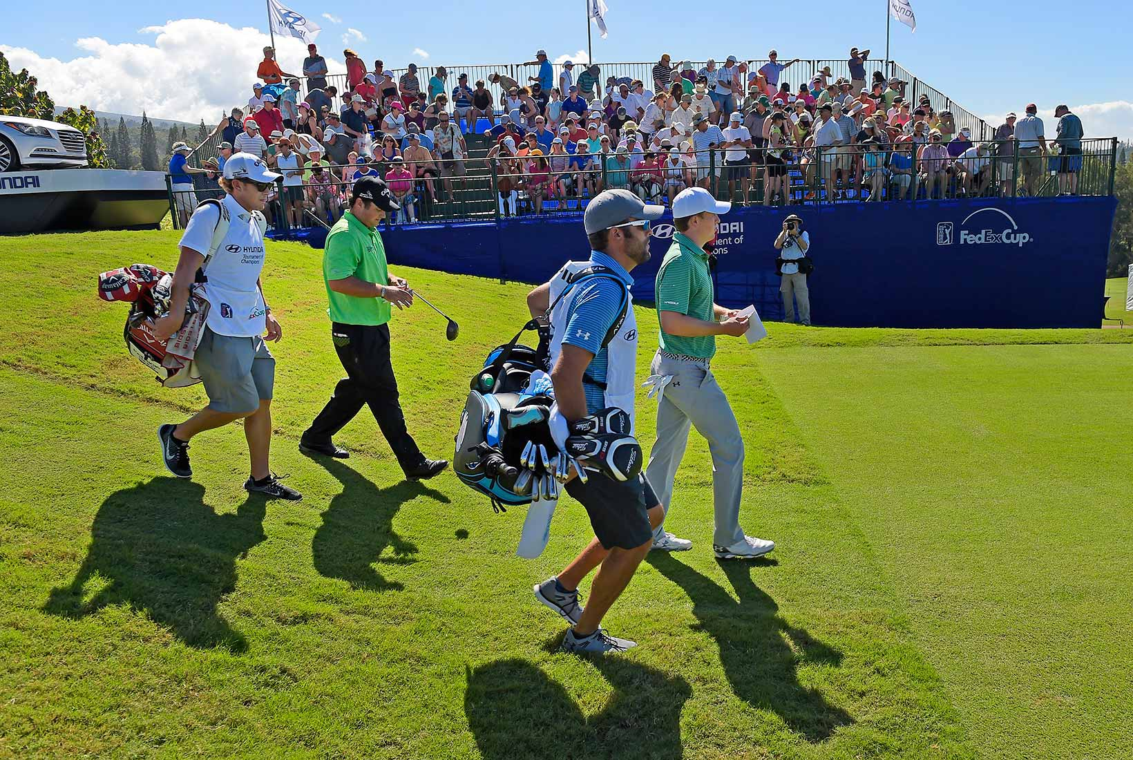 Jordan, Patrick Reed and Caddies Walk Off the First Tee During the First Round